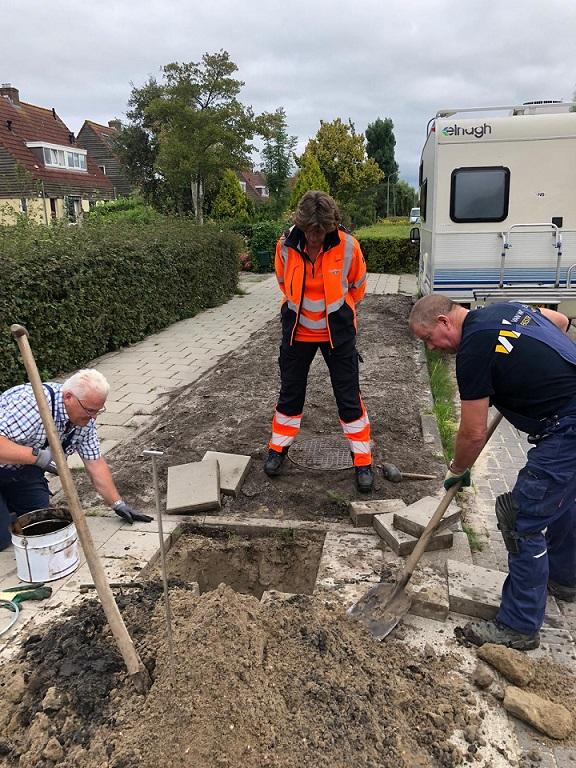 Burgemeester bekijkt een verstopt riool in Broek in Waterland