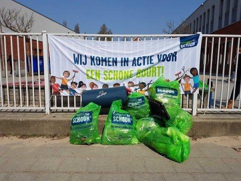 Gevulde afvalzakken en een spandoek met de tekst: wij komen in actie